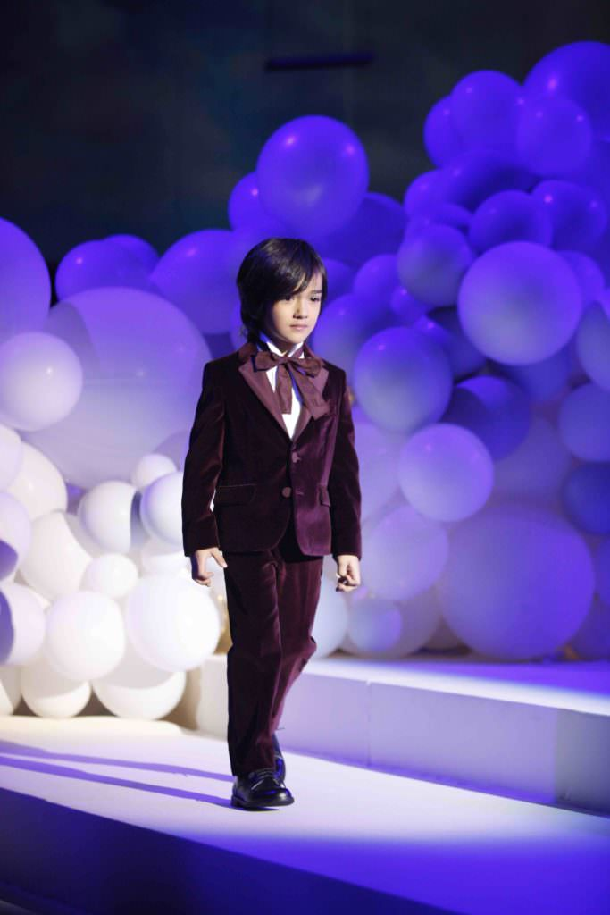 Beautiful velvet burgundy suit for boys fashion against a background of hundreds of white balloons at the Il Gufo winter 2017 show