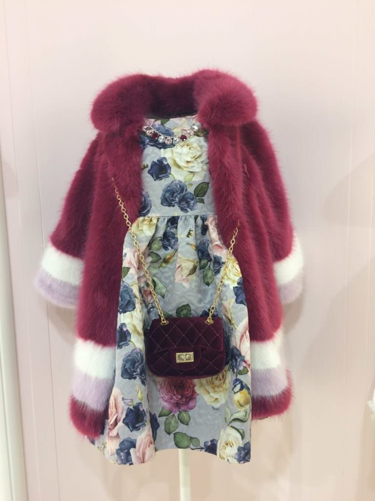 Monnalisa showed the new fake fur look for girls with a triple band at the hem and a large print floral dress at
