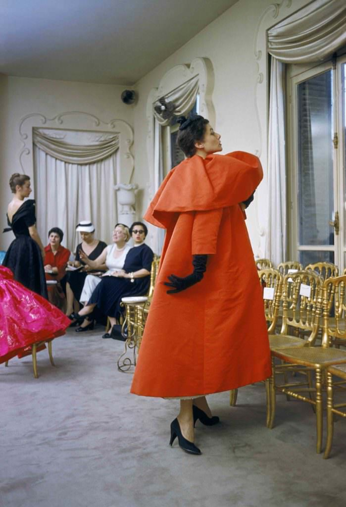 Model wearing Balenciaga-coat as I. Magnin buyers inspect a dinner outfit in the background,Paris 1954-by Mark Shaw / mptvimages.com