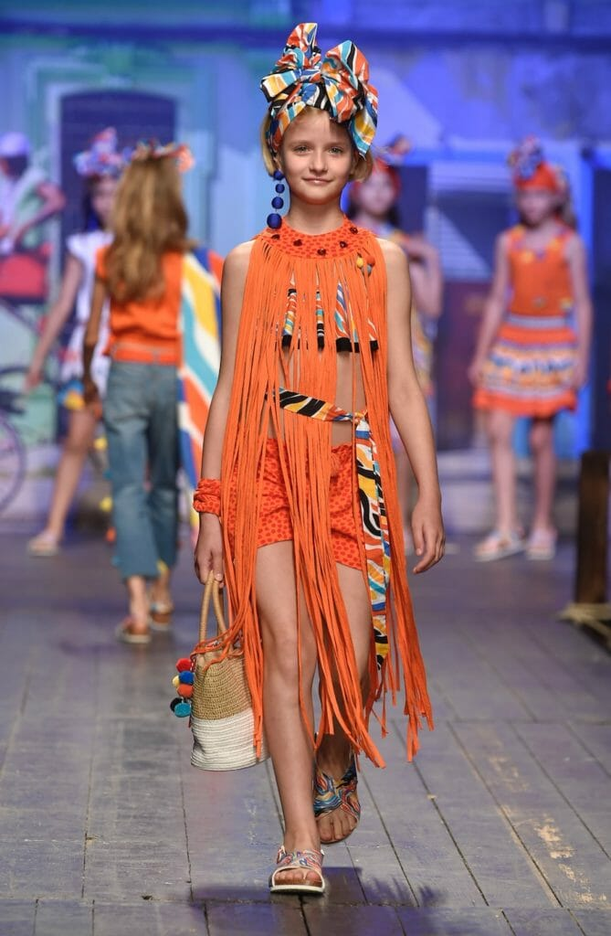 Hot orange, Latin American styling and fringing at TucTuc in the childrens fashion from Spain catwalk at Pitti Bimbo 87 for SS19