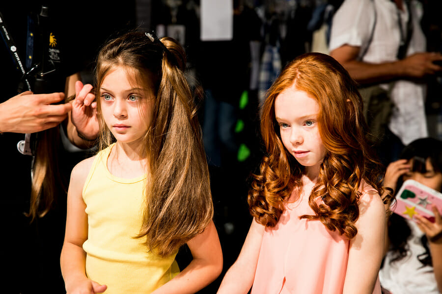 Two young models at Pitti Bimbo 87 KidsFizz show waiting on hair and make up