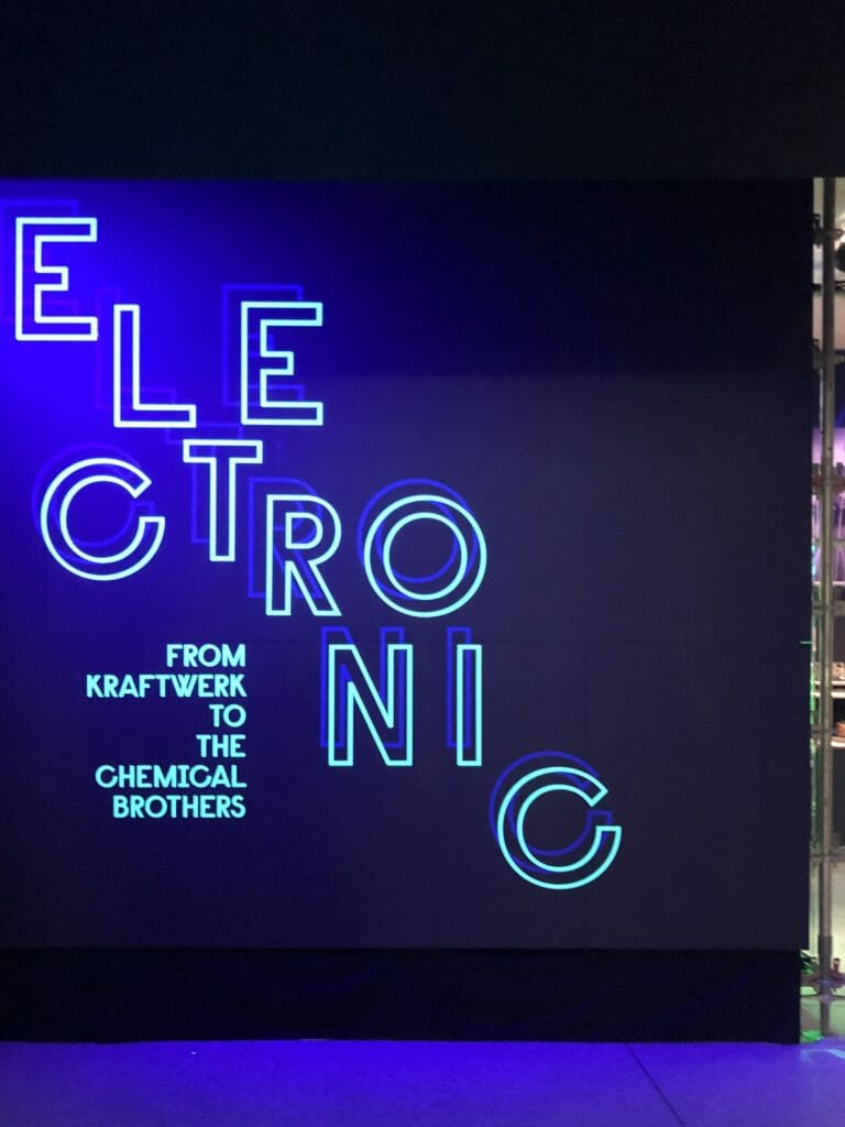 A cool blue neon wall at the entrance to Electronic: From Kraftwerk to The Chemical Brothers